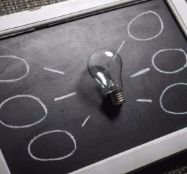 Lightbulb on a chalkboard with idea bubbles drawn branching off from it